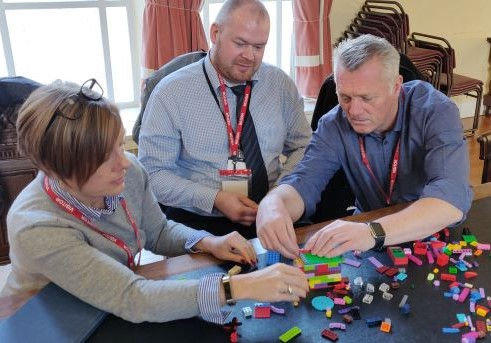 3 adults using lego during an agile training workshop