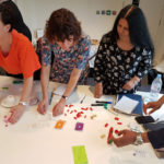 4 adults playing with lego and planning poker cards at an agile training workshop