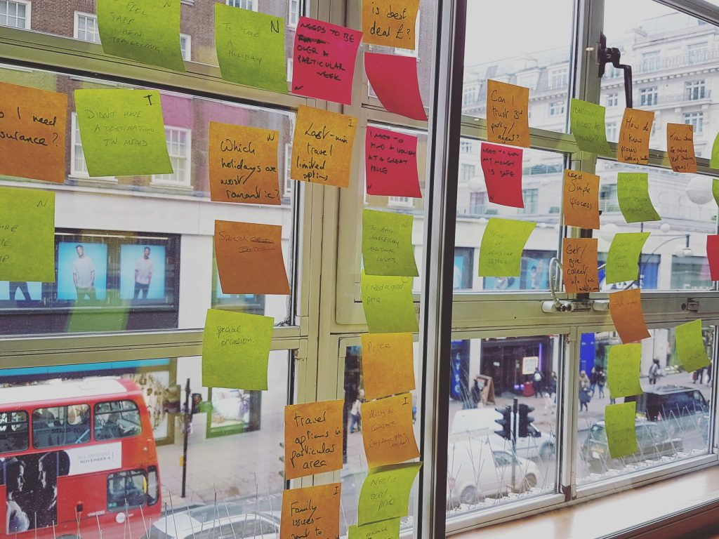Post it notes stuck on a window with a red London bus in the background