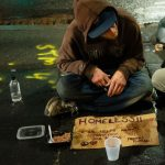 Homeless person with a cardboard sign