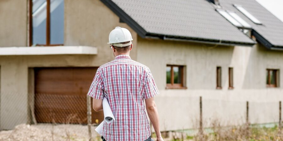 Man with hard hat and building plans looking at a building